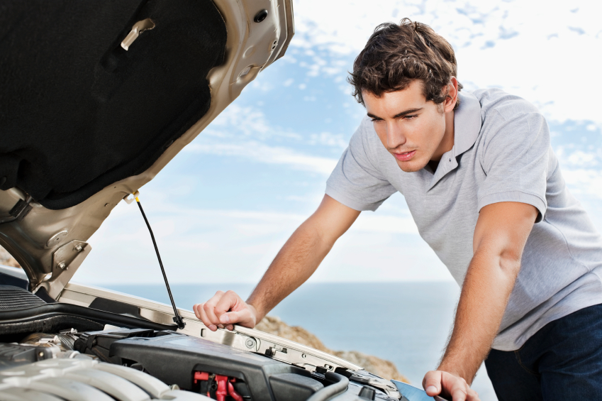 Young man looks under the hood of his car for engine trouble. Horizontal shot.